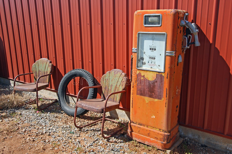 Retro- Gaspumpe und verrostete Stühle stockbild