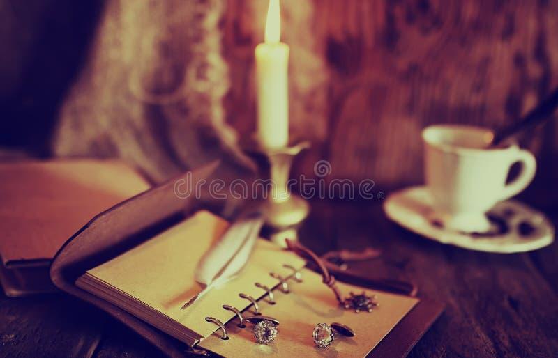 Retro- Gegenstände versehen und leaher Buch mit Kerzenlicht mit Federn lizenzfreies stockfoto