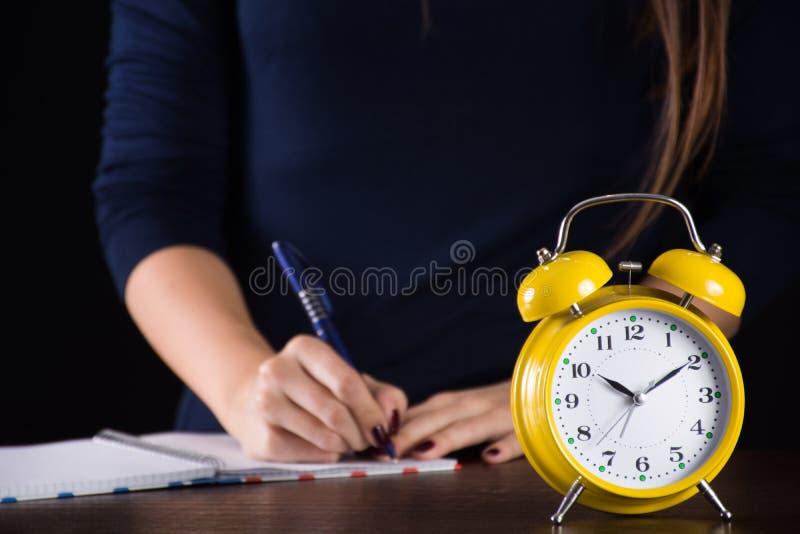 Retro gele oude klok en vrouw in het achtergrond schrijven stock fotografie