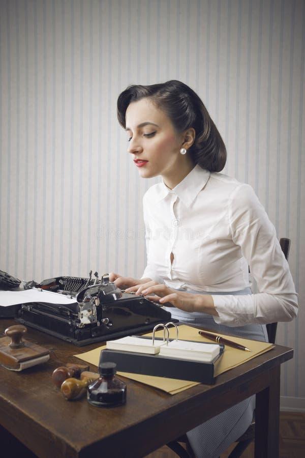 Frau, die in ihrem Büro schreibt stockbild