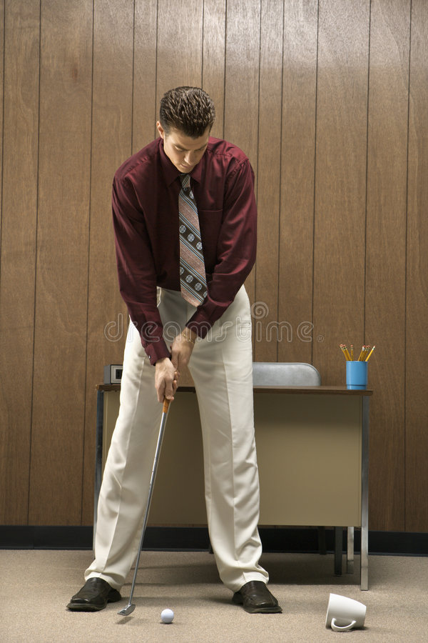 Retro- Geschäftsmann, der Golf im Büro spielt. lizenzfreies stockbild