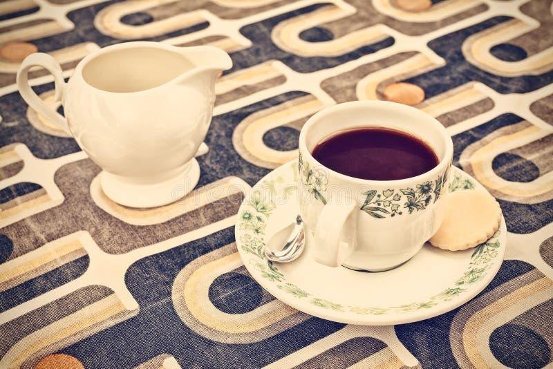 Retro gestileerde beeld van een kop van koffie en melk kan stock afbeelding