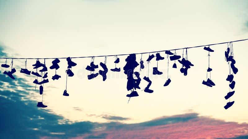 Retro gestileerde silhouetten van schoenen die op kabel hangen royalty-vrije stock afbeeldingen