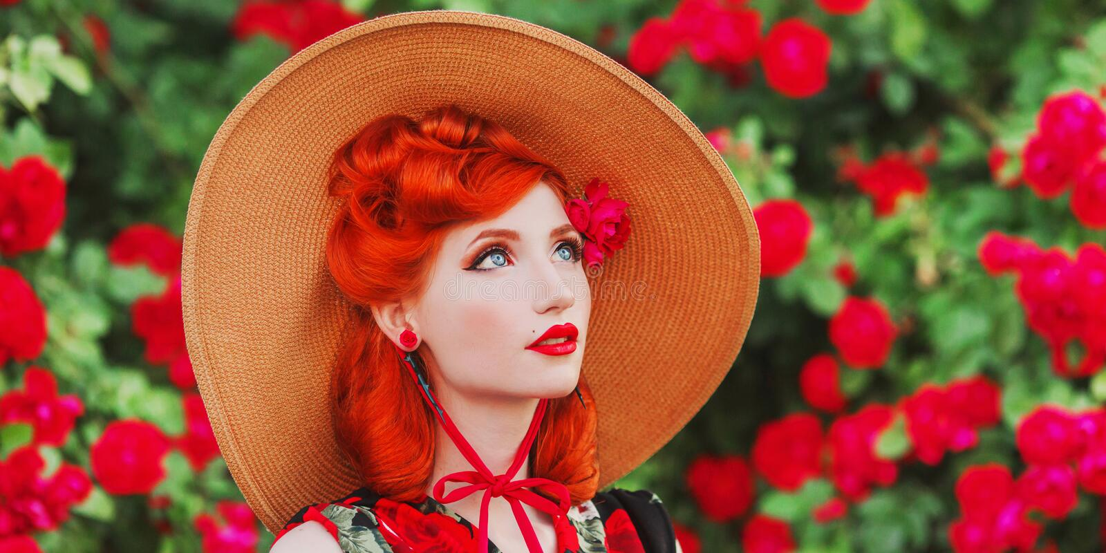 Retro girl with red lips in rose dress on beautiful flower background. Young redhead model in a hat on a background of blossom stock image