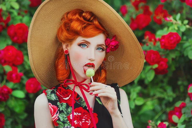 Retro girl with red lips in a dress with a print of roses with yellow lollipop on summer background. Young redhead model in a hat. On a background of a bush of stock photography