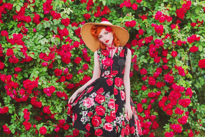 Retro girl with red lips in stylish dress with a print of roses on a beautiful summer background. Young redhead model in a hat on stock image