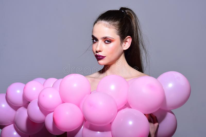 Retro girl with stylish makeup and hair. Fashion woman with many pink air balloons. Birthday decor and celebration stock photos