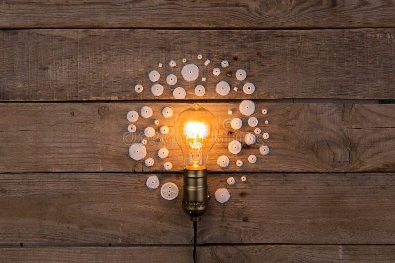 Retro- Glühlampe und Gruppe Gänge auf hölzernem Hintergrund - Idee, stockbilder