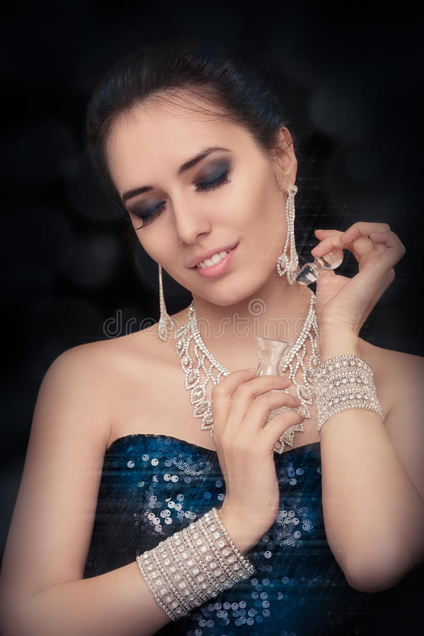 Retro glamour woman holding vintage perfume bottle wearing silver accessories stock image