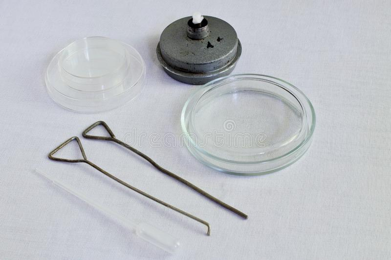 Retro. Glass Petri dishes, metal spirit lamp, metal loops and plastic pipette for the collection of biological fluids for bacterio. Rare medical supplies for stock image