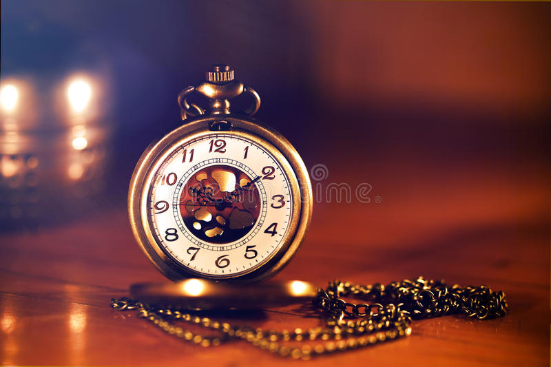 Retro gold pocket watch in beautiful candle light on brown back. Retro gold pocket watch in beautiful light candle on brown background stock photo