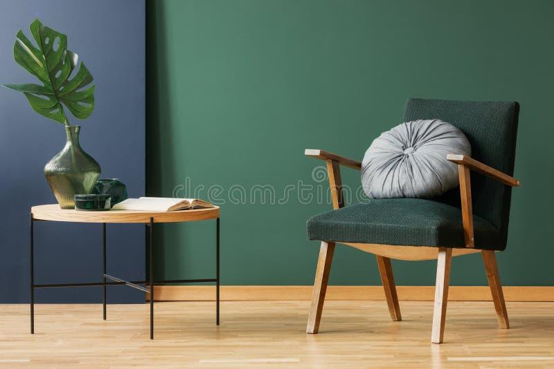 Retro grön fåtölj för mossa med rundan, silverkudde bredvid träkaffetabellen med bladet i exponeringsglasvasen, kopieringsutrymme arkivfoto