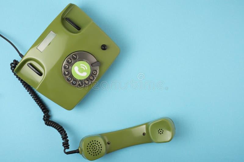 Retro- grünes Telefonfoto auf einem blauen Hintergrund stockfotografie