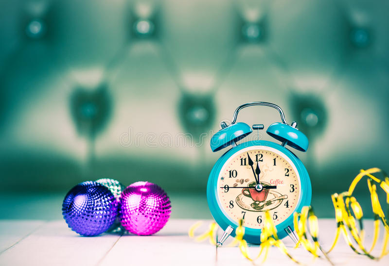Retro green alarm clock with five minutes to midnight. royalty free stock image