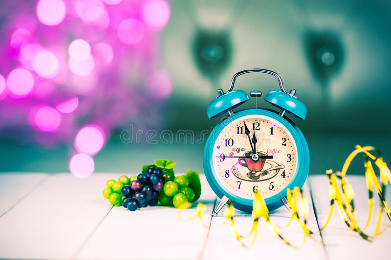 Retro green alarm clock with five minutes to midnight. stock images