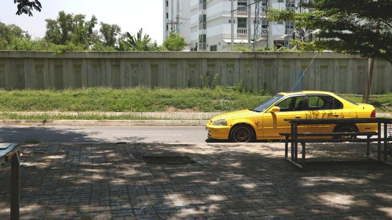Retro gul bilparkering på gatan med den tomma Pavement/trottoaren arkivfoto