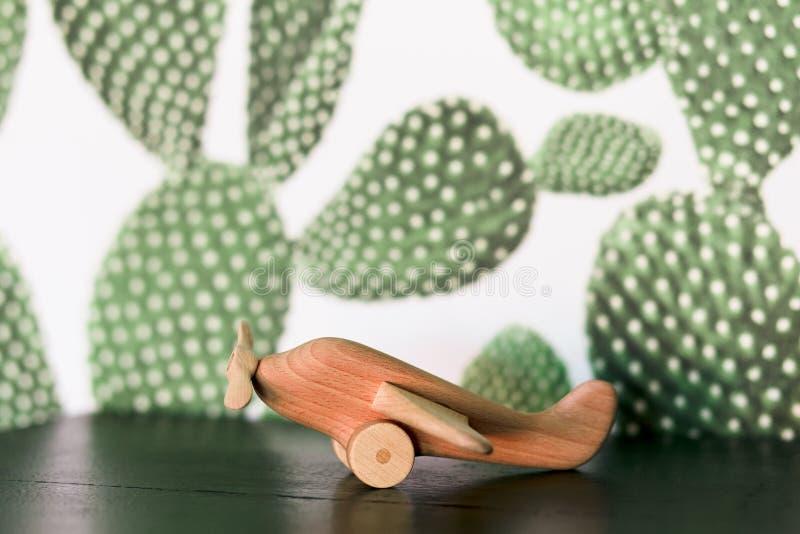 Retro- hölzernes Spielzeugflugzeug auf Tabelle mit Kaktushintergrund lizenzfreie stockfotos