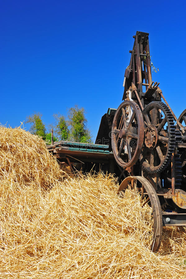 Retro Hay Bailer. A restored and operational 1918 Hay bailer next to a stack of straw fresh from the thrasher with a deep blue sky in the background royalty free stock photography