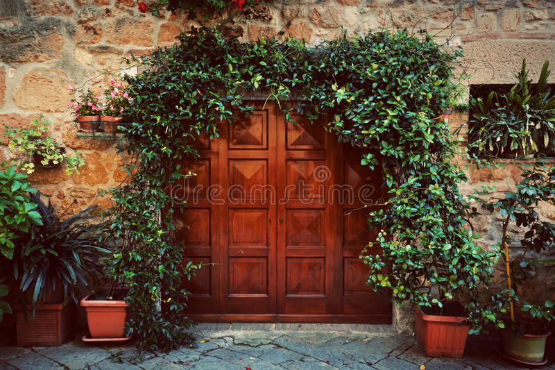 Retro houten deur buiten oud Italiaans huis in een kleine stad van Pienza, Italië wijnoogst stock afbeelding
