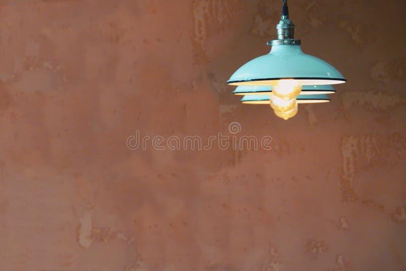 Retro ilumine - a lâmpada de suspensão azul na parede vazia marrom imagens de stock