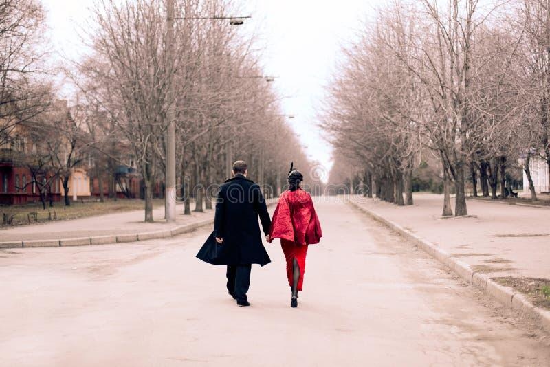 Retro-, im altem Stil, Paare, Mädchen und Mann, die hinunter die Straße, ein rotes Kleid und einen Mantel tragend geht lizenzfreie stockfotos