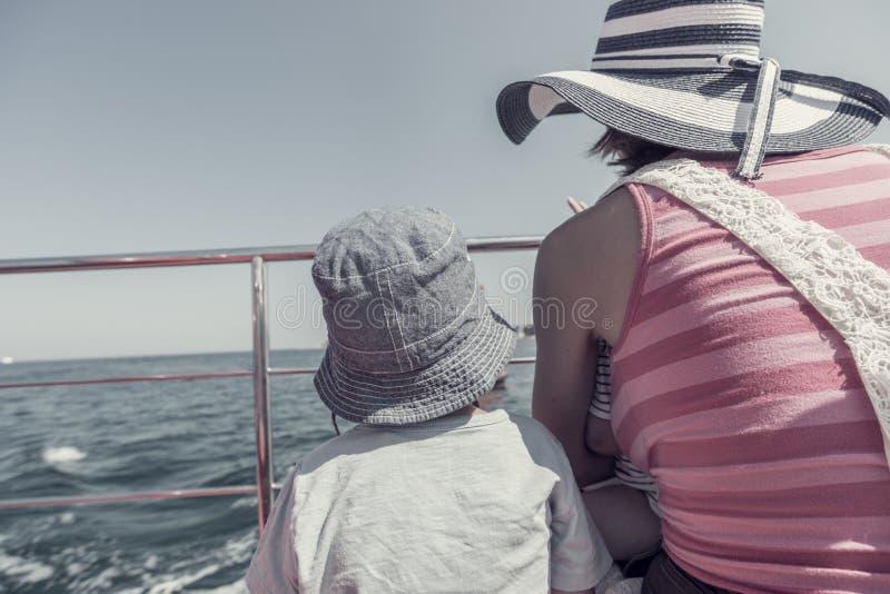 Retro immagine del bambino e della donna sulla piattaforma di barca durante il vacati di estate fotografia stock