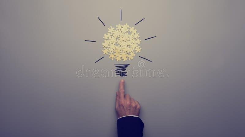 Retro immagine tonificata di un uomo d'affari che indica su un tiraggio della lampadina immagini stock