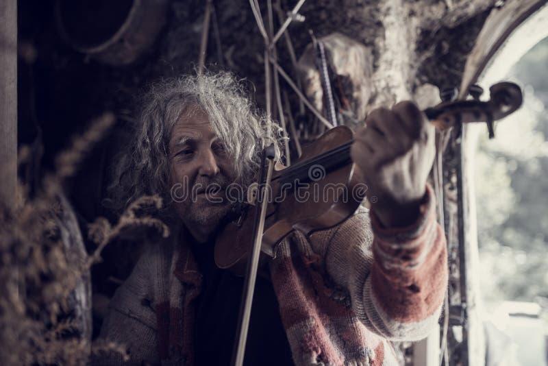 Retro immagine tonificata di un uomo in un maglione stracciato p piena di buchi fotografia stock libera da diritti