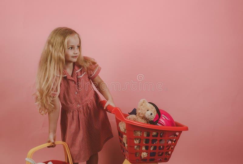 Retro inspirowany Trochę shopaholic z wózek na zakupy mały dziewczyna zakupy Mała dziewczyna w sklepie Mały kupujący tła pięknej  zdjęcia stock