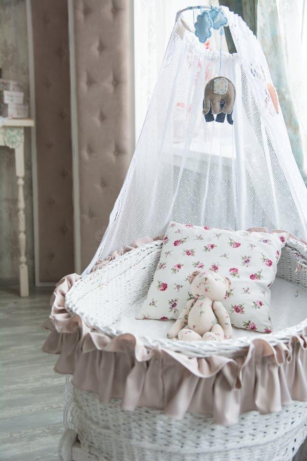 Retro interior children's bedroom with a wicker crib and teddy b stock photo