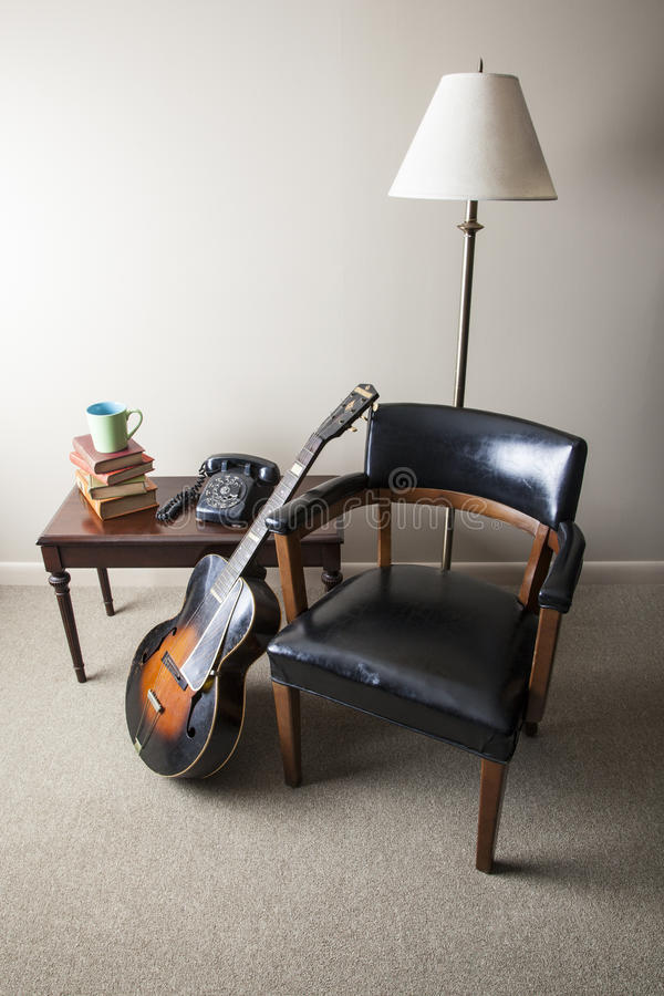 Retro Interior - Window Light. A retro style interior photo is shown with a mid-century modern chair, old books, coffee mug, accoustic guitar, and black rotary stock images