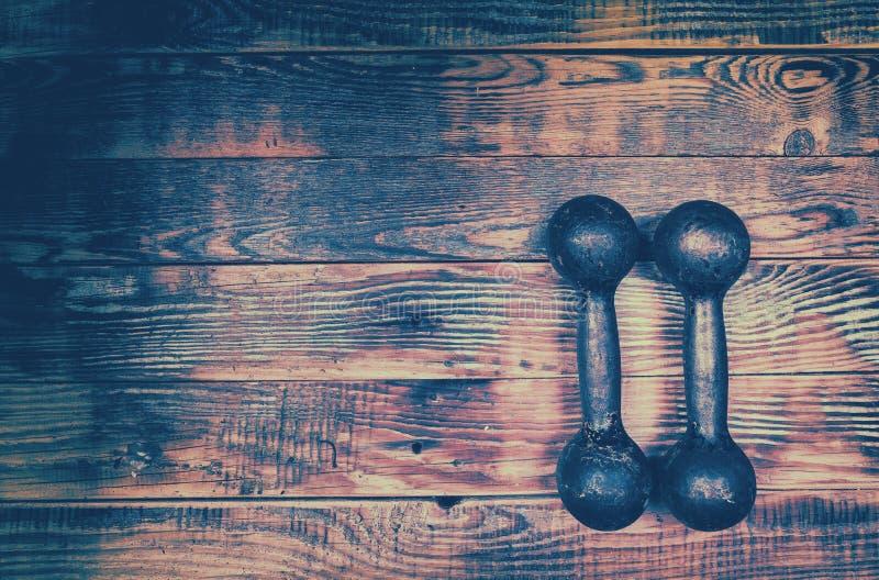 Retro iron dumbbells on wooden background stock image