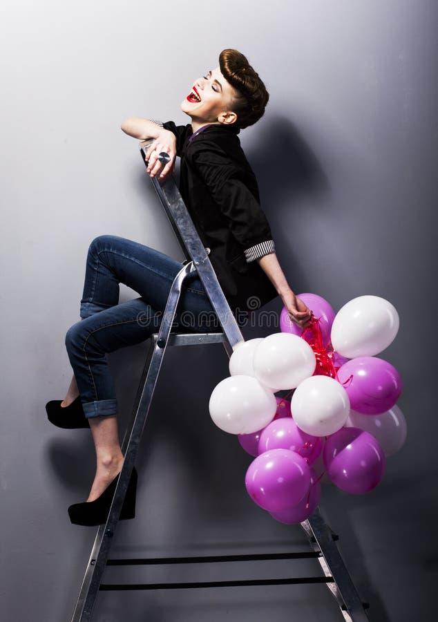 Retro- jugendlich Mädchen der hübschen Art und Weise, das auf Strichleiter lacht lizenzfreies stockbild