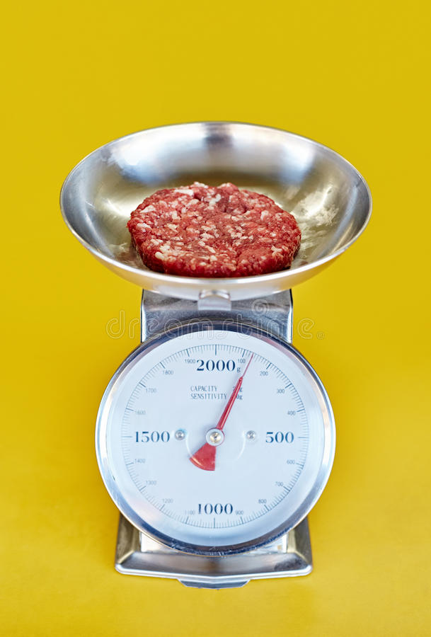 Retro- Küchenskala mit dem frischen gehackten roten Fleisch, das gewogen wird stockbild