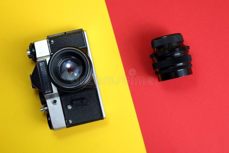 Retro Kamera Alte Filmkamera- und -linsenlügen auf einem roten und gelben Hintergrund stockfotos