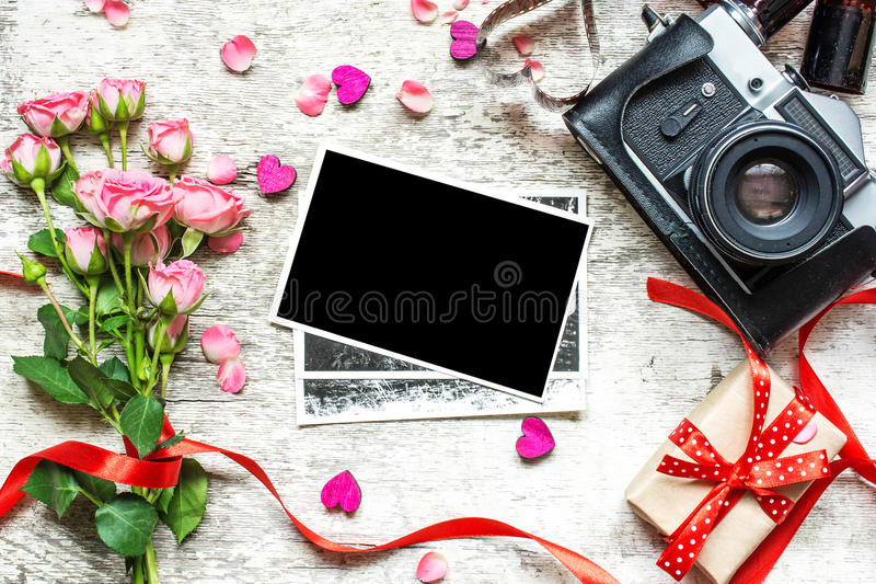 Retro- Kamera der Weinlese mit Fotos und Blumen der freien Räume stockfotos