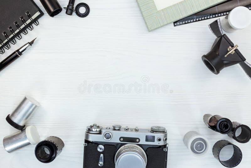 Retro kamera, ekranowe rolki, obiektyw, pusta fotografii rama na białym woode zdjęcie royalty free