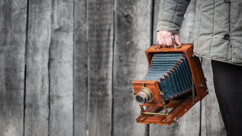 Retro kamera för stort format i fotografhand Begrepp - fotografi av 1930sen-1950s Retro trävägg på bakgrund, arkivbilder