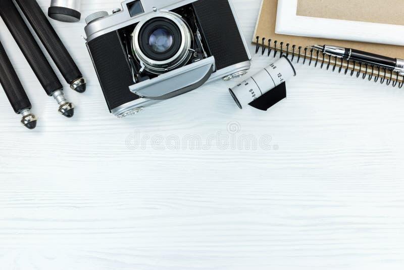 Retro- Kamera, Filmstreifen, Stativ, Notizbuch und Stift auf weißem woode stockfoto