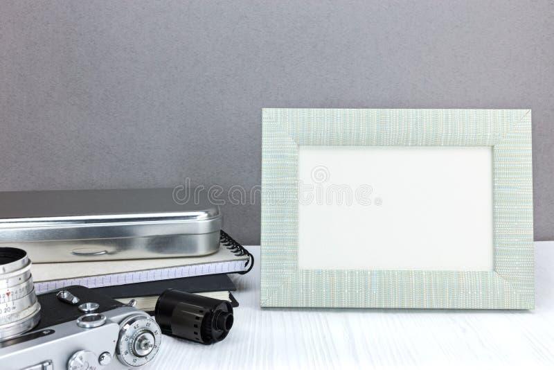 Retro kamera, negatywna ekranowa rolka i pusta fotografii rama na popielatym b, zdjęcia stock