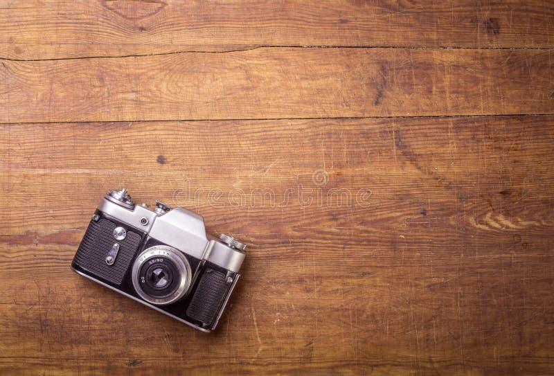 Retro kamera på wood tabellbakgrund arkivfoto