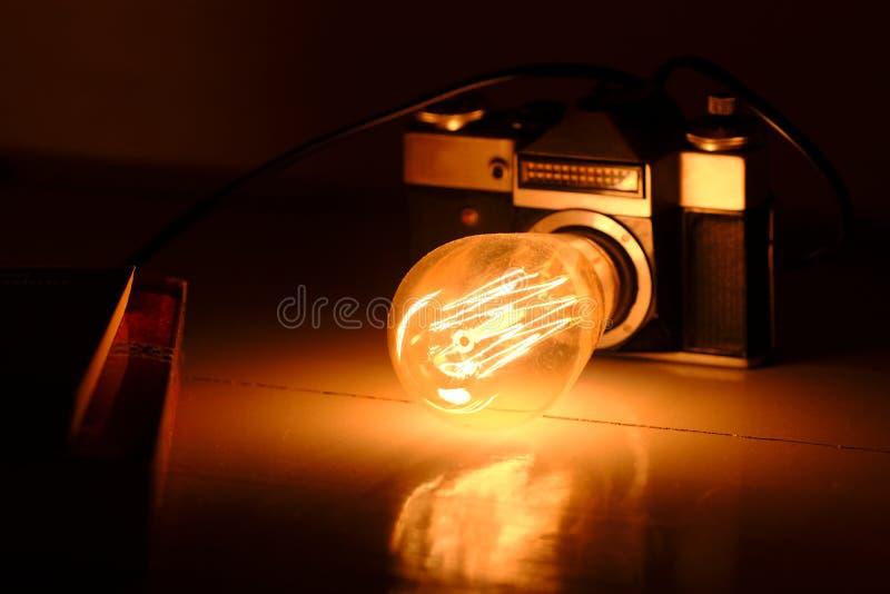 Retro- Kamera, warme Edison-Birne lizenzfreie stockbilder