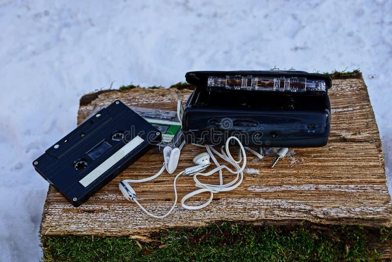 Retro- Kassette und schwarzer Spieler auf einem Klotz mit Moos im Schnee lizenzfreies stockbild