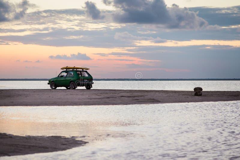 Retro kipiel samochód z surfboard na piaska barze blisko oceanu z słońca położeniem w tle zdjęcie royalty free