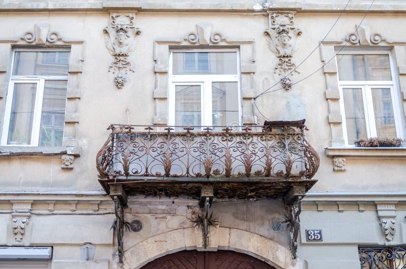 Retro klassiska smidesjärnbalkonger för gammal tappning av metall med färgmodeller på en gammal tegelstenbyggnad med fönster arkivfoto