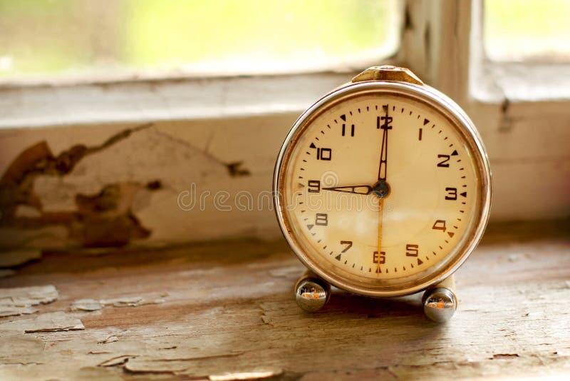 Retro klocka på fönsterfönsterbrädan royaltyfri foto