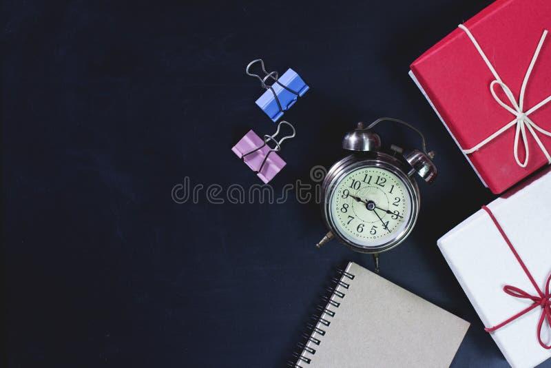 Retro klok met van het giftdoos en bureau levering op bord stock afbeeldingen