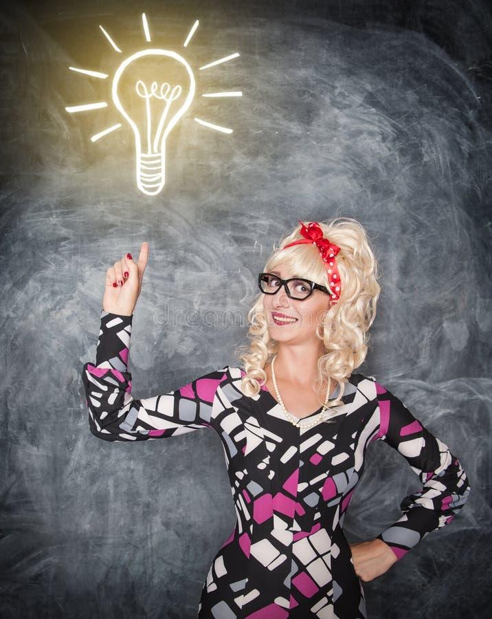 Retro kobieta pokazuje na rysunkowej lampie palcem obrazy stock