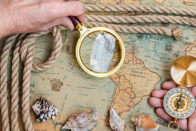 Retro kompass för gammal tappning, förstoringsglas på forntida världsmor royaltyfri foto