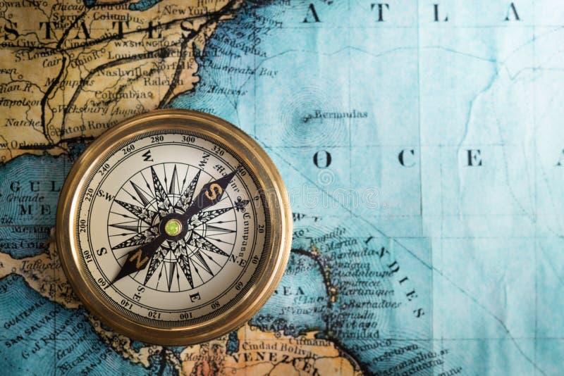 Retro kompass för gammal tappning på forntida översiktsbakgrund Loppgeog royaltyfri fotografi